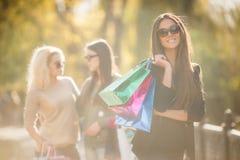 Femme heureuse avec des achats sur un fond des amis Photographie stock libre de droits