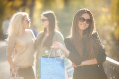 Femme heureuse avec des achats sur un fond des amis Images libres de droits