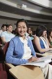 Femme heureuse avec des amis dans la salle de classe Photo stock