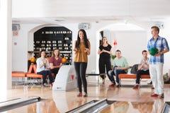 Femme heureuse avec des amis dans le club de bowling Photos stock