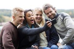 Femme heureuse avec des amis prenant l'autoportrait au terrain de camping Photos stock