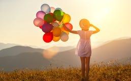 Femme heureuse avec des ballons au coucher du soleil en été photos stock