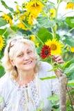 Femme heureuse avec des fleurs dans son jardin Images stock