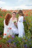 Femme heureuse avec des fleurs de champ et des filles mignonnes jouant dans le blo Image libre de droits