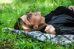Femme heureuse avec des lunettes de soleil se trouvant sur une couverture dans l'herbe de pré le jour ensoleillé de ressort photographie stock
