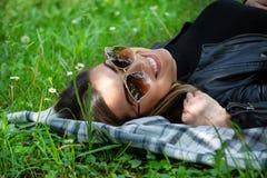 Femme heureuse avec des lunettes de soleil se trouvant sur une couverture dans l'herbe de pr? le jour ensoleill? de ressort photos libres de droits