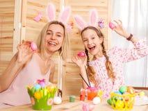 Femme heureuse avec des oeufs de pâques de peinture d'enfant Images stock