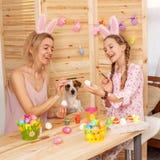 Femme heureuse avec des oeufs de pâques de peinture d'enfant Photographie stock libre de droits