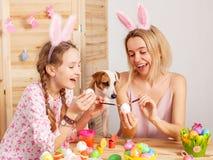 Femme heureuse avec des oeufs de pâques de peinture d'enfant Photo stock