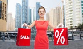Femme heureuse avec des paniers au-dessus de ville du Dubaï Image libre de droits