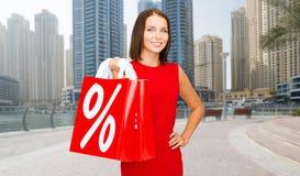 Femme heureuse avec des paniers au-dessus de ville du Dubaï Photographie stock libre de droits