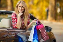 Femme heureuse avec des paniers dans la voiture convertible Photo libre de droits