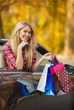 Femme heureuse avec des paniers dans la voiture convertible Images libres de droits