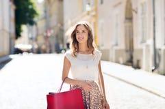 Femme heureuse avec des paniers marchant dans la ville Photographie stock libre de droits