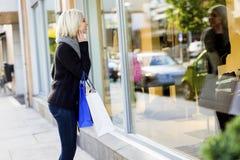 Femme heureuse avec des paniers regardant dans la fenêtre de boutique Photographie stock