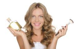 Femme heureuse avec du cosmétique pour la peau et la brosse Images stock
