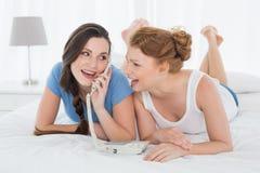 Femme heureuse avec l'ami à l'aide du téléphone dans le lit Image stock