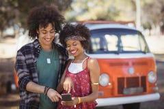 Femme heureuse avec l'ami à l'aide du téléphone sur le champ Photos libres de droits
