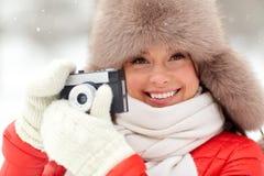 Femme heureuse avec l'appareil-photo de film dehors en hiver Photographie stock libre de droits