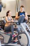 Femme heureuse avec l'entraîneur sur le vélo d'exercice dans le gymnase Photo stock