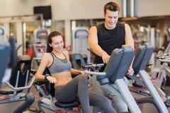 Femme heureuse avec l'entraîneur sur le vélo d'exercice dans le gymnase Images stock