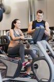 Femme heureuse avec l'entraîneur sur le vélo d'exercice dans le gymnase Photographie stock libre de droits
