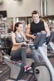 Femme heureuse avec l'entraîneur sur le vélo d'exercice dans le gymnase Image stock