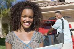 Femme heureuse avec l'homme maintenant le bagage dans la voiture Photos libres de droits