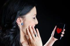 Femme heureuse avec l'image de coeur au téléphone Image stock