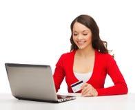 Femme heureuse avec l'ordinateur portable et la carte de crédit Image stock