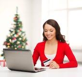 Femme heureuse avec l'ordinateur portable et la carte de crédit Images stock