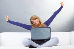 Femme heureuse avec l'ordinateur portable se reposant sur le sofa et étirant ses mains photos libres de droits