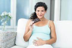 Femme heureuse avec la barre de chocolat sur le sofa Photo stock