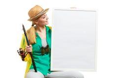 Femme heureuse avec la canne à pêche tenant le conseil Photo stock
