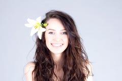 Femme heureuse avec la fleur dans les cheveux bouclés avec le sourire avec des dents Station thermale - 7 Photographie stock