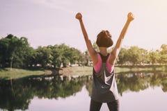 femme heureuse avec la main d'exposition haute et la position photographie stock libre de droits