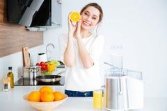 Femme heureuse avec la moitié orange faisant le jus frais Image libre de droits