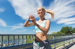 Femme heureuse avec la montre et les écouteurs de fréquence cardiaque photographie stock