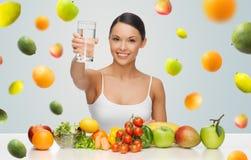 Femme heureuse avec la nourriture saine montrant le verre d'eau Photos stock