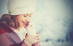 Femme heureuse avec la tasse de la boisson chaude l'hiver froid dehors Photos stock