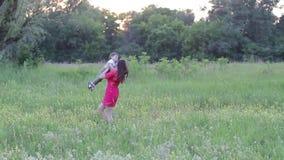 Femme heureuse avec le bébé un jour ensoleillé d'été La famille marche par le pré banque de vidéos