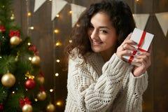 Femme heureuse avec le boîte-cadeau dans la décoration de Noël Intérieur en bois foncé avec des lumières Soirée et concept romant Photos stock