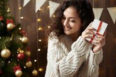Femme heureuse avec le boîte-cadeau dans la décoration de Noël Intérieur en bois foncé avec des lumières Soirée et concept romant Images stock