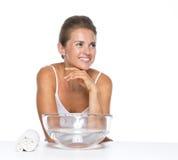Femme heureuse avec le bol en verre avec de l'eau regardant sur l'espace de copie Photo stock