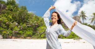 Femme heureuse avec le châle ondulant en vent sur la plage image stock