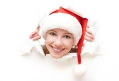 Femme heureuse avec le chapeau de Noël jetant un coup d'oeil par un trou déchiré en affiche de livre blanc Images libres de droits