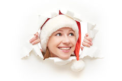 Femme heureuse avec le chapeau de Noël jetant un coup d'oeil par un trou déchiré en affiche de livre blanc Photos stock