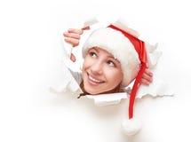 Femme heureuse avec le chapeau de Noël jetant un coup d'oeil par un trou déchiré en affiche de livre blanc Photographie stock