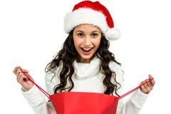 Femme heureuse avec le chapeau de Noël ouvrant le panier rouge images libres de droits