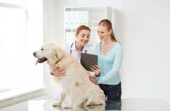 Femme heureuse avec le chien et le docteur à la clinique de vétérinaire image libre de droits